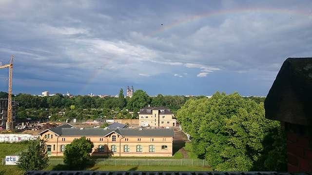 Domblick: Regenbogen über der Stadt nach Gewitter